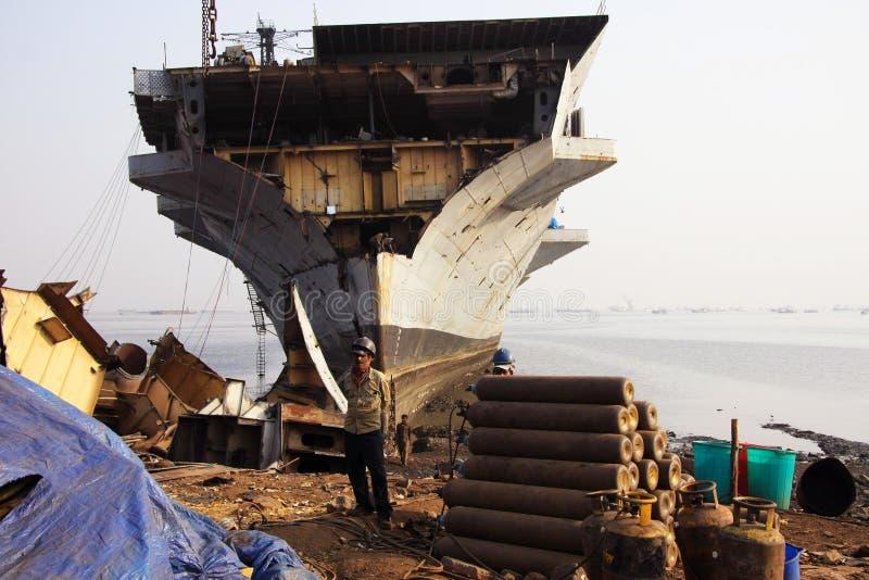 Mumbai/India - 23/11/14 - Ship Breaker stood in front of INS Vikrant in Darukhana Ship Breaking Yard royalty free stock images
