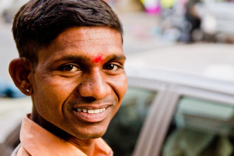 Mumbai Indien - 20 juni 2018: ung indisk man som framme ler i camere i det friagatan i staden med röd tilaka royaltyfri bild