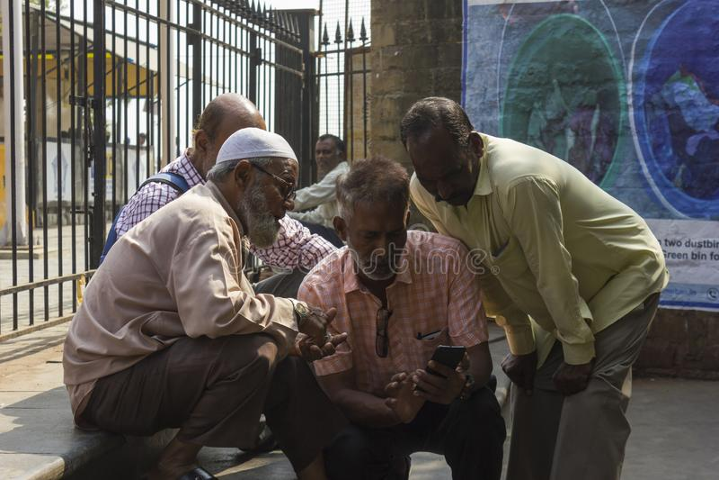 Mumbai, maharashtra, India 05-10-2019 Uomini della religione differente che controllano il punteggio del cricket in un telefono c immagini stock libere da diritti