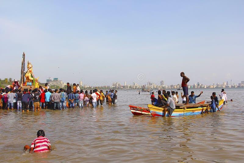 MUMBAI, MAHARASHTRA, septembre 2017, les gens portent l'idole de Ganapati pour l'immersion dans la mer dans des bateaux en bois c image libre de droits