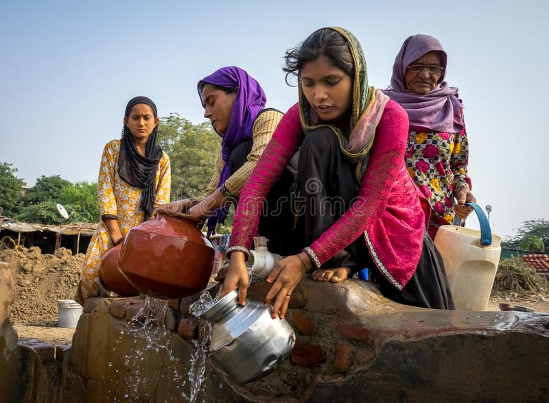 Mumbai women filling water pots. Group of women in the Mumbai slums of India filling up water pots with fresh water stock photography