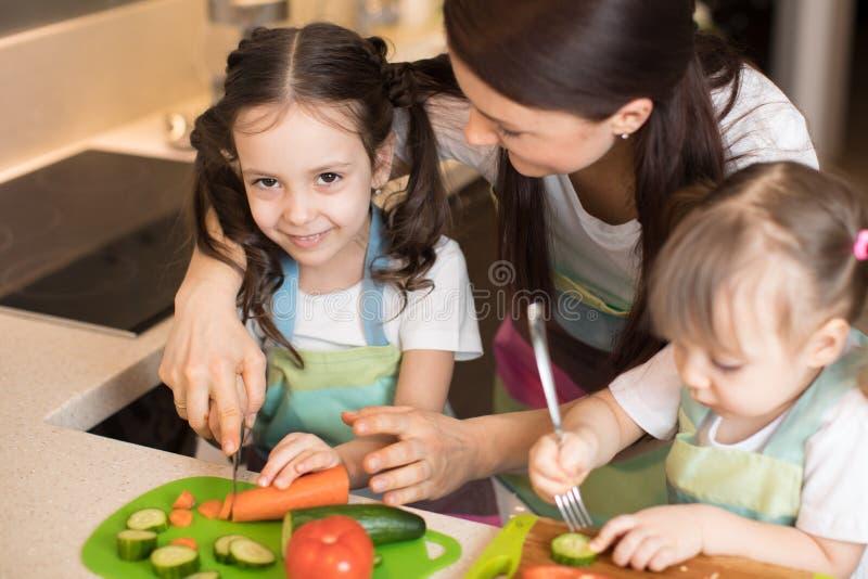 Mumhuggande grönsaker med barndöttrar i ett familjehushåll arkivfoton