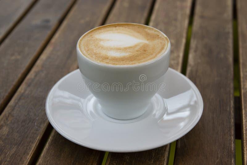 Mumm von leckerem Cappuccino auf einem Holztisch lizenzfreies stockfoto