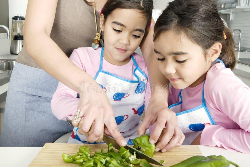 Mummia e figlia che tagliano le verdure a pezzi fotografie stock libere da diritti