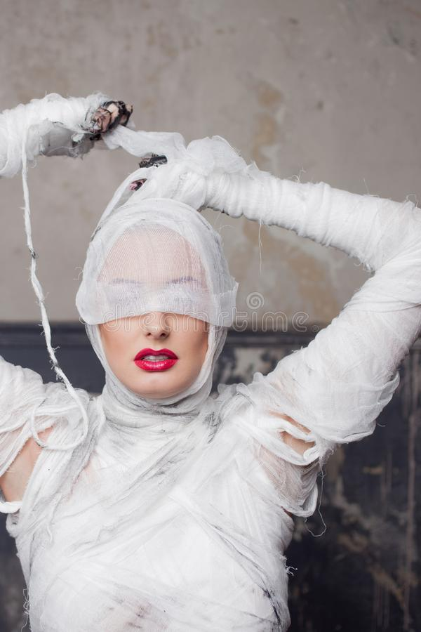 Mummy girl blindfolded. Portrait of a young beautiful woman in bandages all over her body. royalty free stock photography