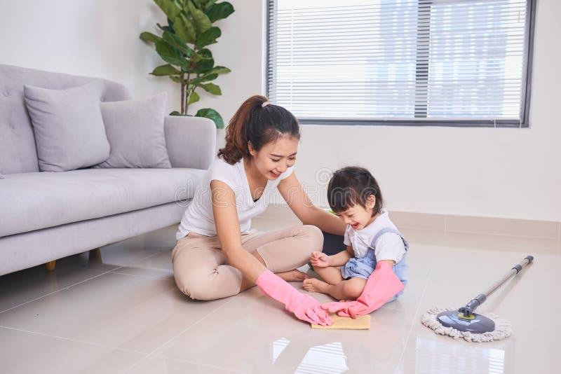 Mumundervisningdotter som gör ren deras hem- vardagsrum på helgen royaltyfri fotografi