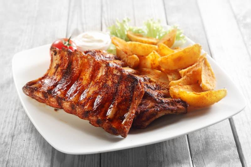 Mund, der gegrillte Schweinefleisch-Rippe und Fried Potatoes wässert stockbild