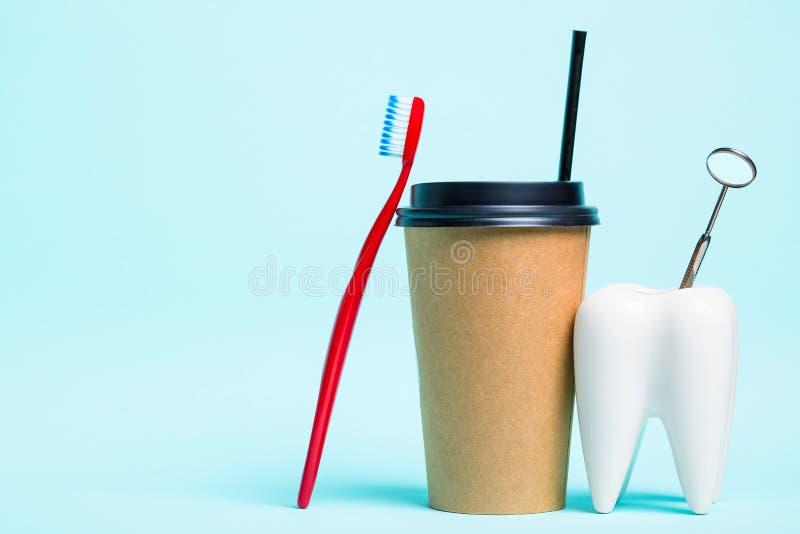 Mundmundpflege Gesunder weißer Zahn- und Zahnarztspiegel nahe Zahnbürste und Thermo PlastikTasse Kaffee auf hellblauem lizenzfreie stockfotografie