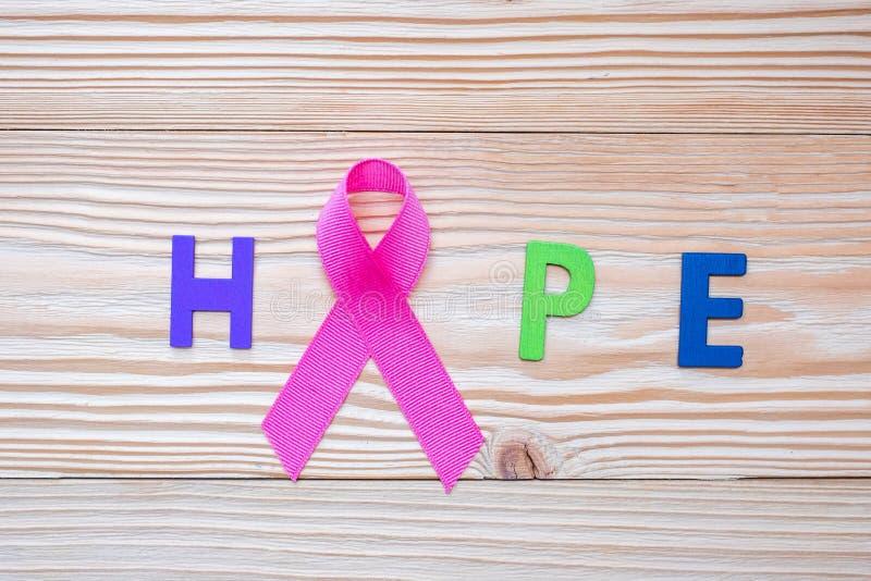 Mundo câncer dia o 4 de fevereiro ou câncer da mama, letra da esperança e fita cor-de-rosa no fundo de madeira para os povos de a foto de stock