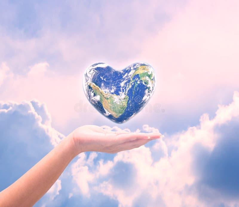 Mundo na forma do coração com mãos humanas das mulheres excedentes no natu borrado imagens de stock royalty free