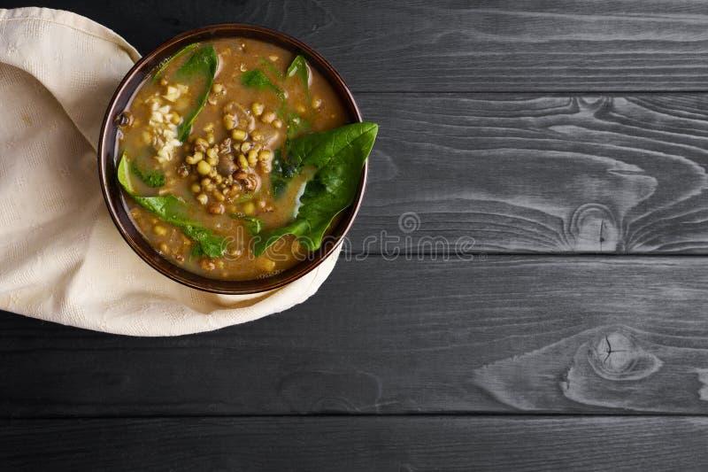 Mung Dhal con spinaci verdi al ripiano del tavolo di legno nero Moong dal - curry indiano di cucina Piatto asiatico vegetariano fotografie stock libere da diritti