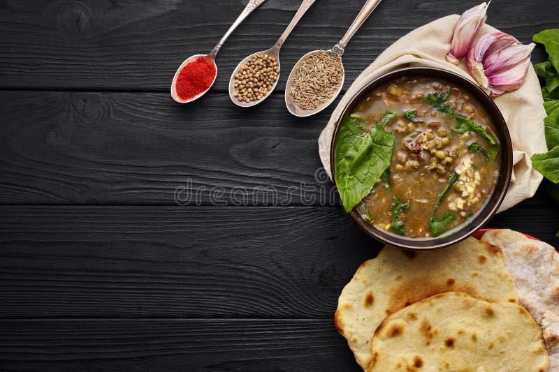 Mung Dhal, spinaci, focaccia, aglio e spezie al ripiano del tavolo di legno nero Moong dal - curry indiano di cucina fotografia stock libera da diritti