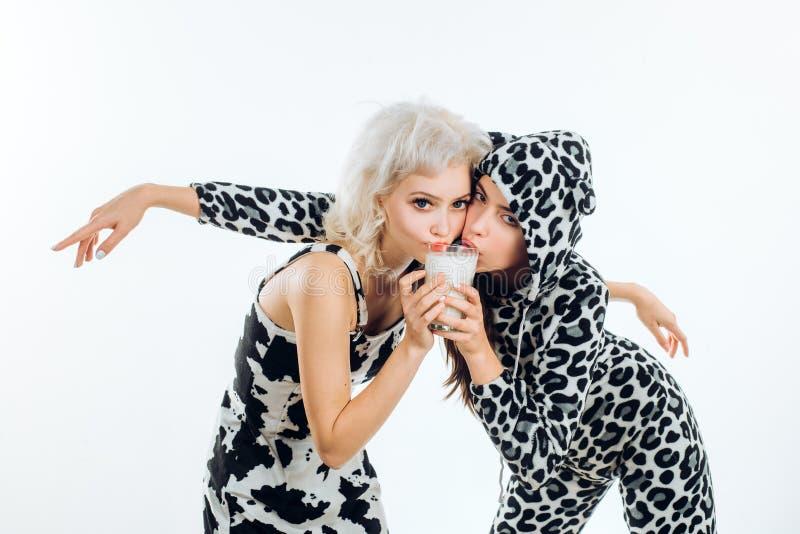Munga ogni momento per tutto il piacere che potete ottenere da  Donne sveglie che bevono latte regolare Tenuta adorabile delle ra fotografia stock