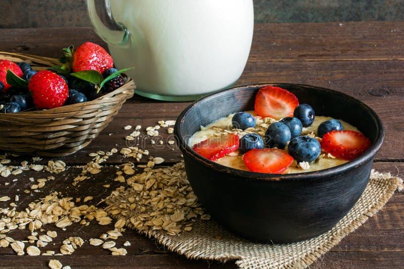 Munga in un porridge della farina d'avena e della brocca in una ciotola delle terraglie con le bacche mature fresche in una cioto fotografia stock