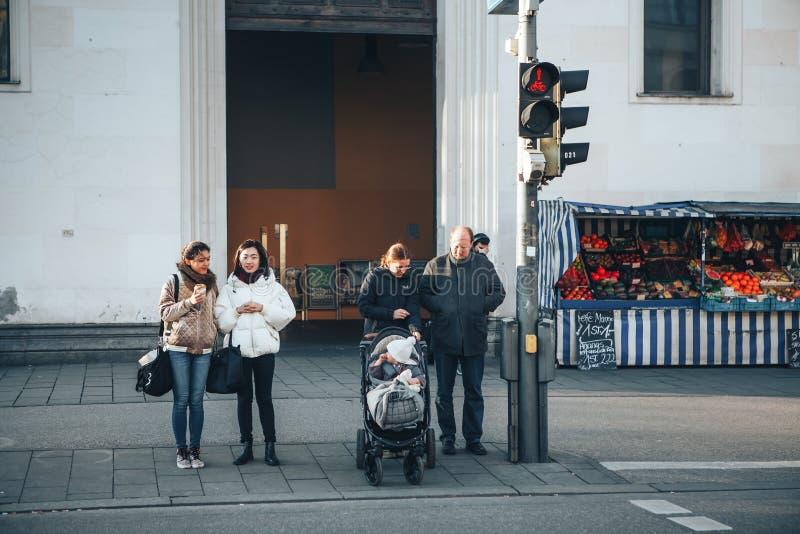 Munich, Alemanha, o 29 de dezembro de 2016: Os povos estão nos sinais e estão prontos para cruzar a estrada Rotina diária fotos de stock