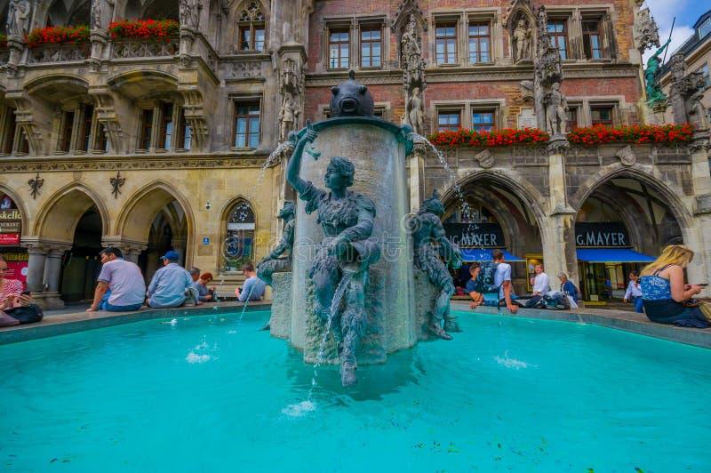 Munich, Alemania - 30 de julio de 2015: Fuente famosa de los pescados situada en la plaza principal fuera del edificio del ayunta fotos de archivo