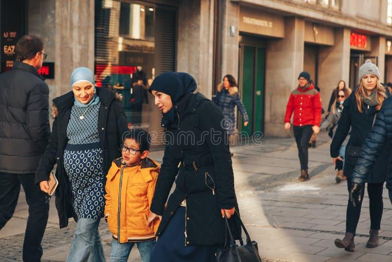 Munich, Alemania, el 29 de diciembre de 2016: Una familia amistosa de nómadas camina abajo de la calle en Munich tolerancia foto de archivo libre de regalías