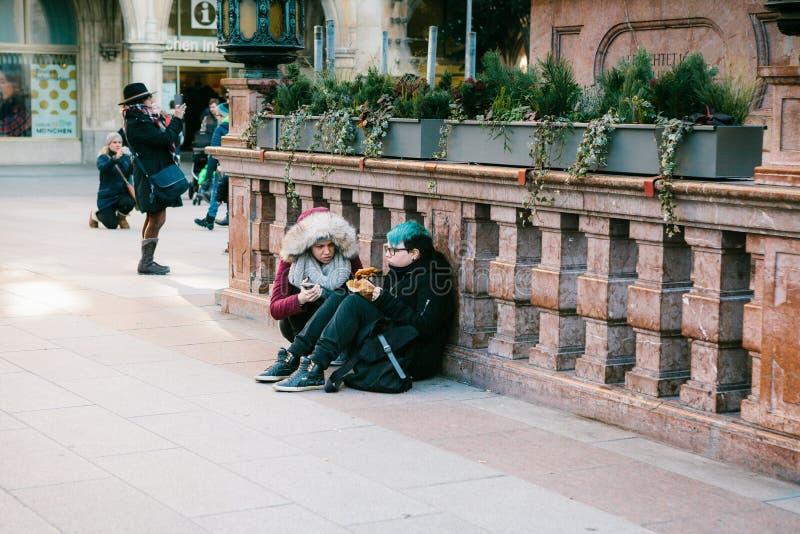 Munich, Allemagne, le 29 décembre 2016 : Deux filles punks s'asseyent et mangent dans la place centrale à Munich subculture journ photo stock