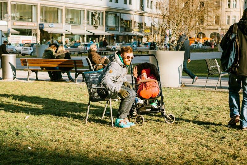 Munich, Allemagne, le 29 décembre 2016 : Le père marche avec un petit enfant dans une poussette en parc au centre de Munich photos stock