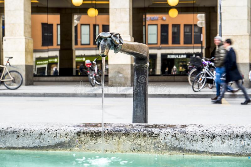 Munich , Germany - February 15 2018 : Water flowing from well while People walking on the Marienplatz.  stock image