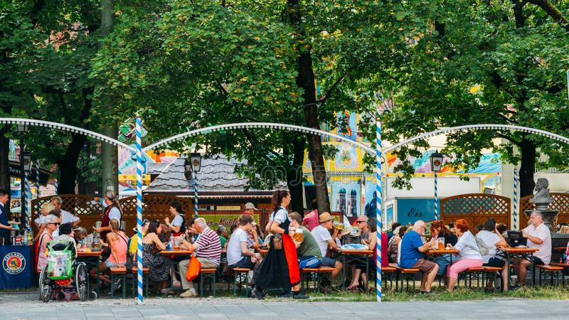 Crowded Bavarian beer garden in the summer with plenty of beer and snacks served royalty free stock photography