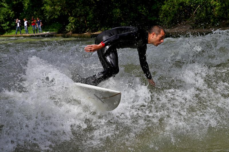 Munich, Germany - July 13, 2019: Surfer in the city river called Eisbach stock photo