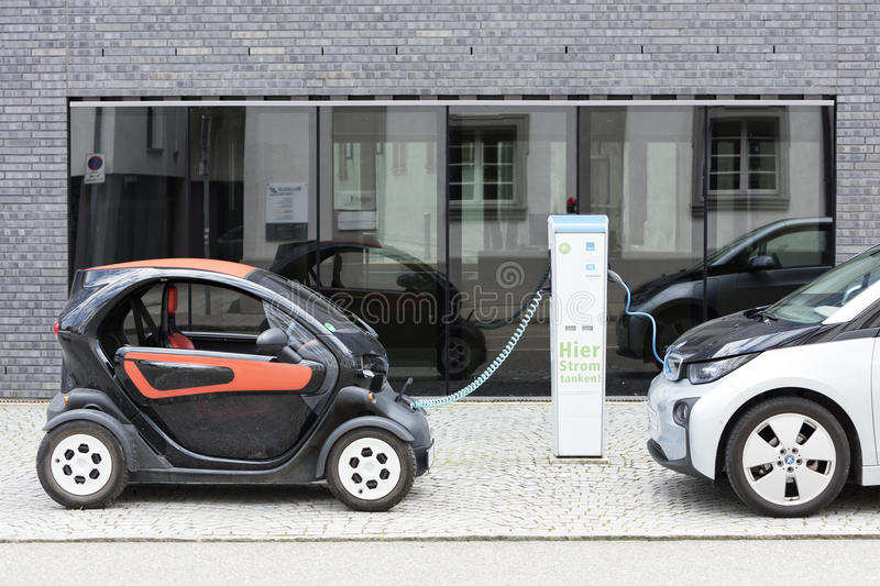 Munich, Germany- June 25, 2016: Two electric cars, Renault and BMW, being recharged at plug-in station in front of modern building. Two electric cars, Renault stock photos