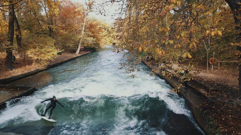 MUNICH, GERMANY, November 18, 2019: Real time shot of Urban Surfers on a wave on the Eisbach river. River Surfing in stock photo