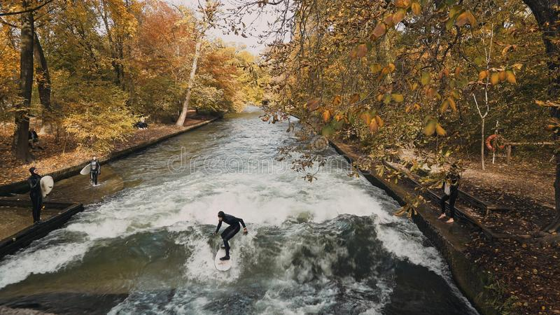 MUNICH, GERMANY, November 18, 2019: Real time wide shot of Urban Surfers on a wave on the Eisbach river. River Surfing royalty free stock photography