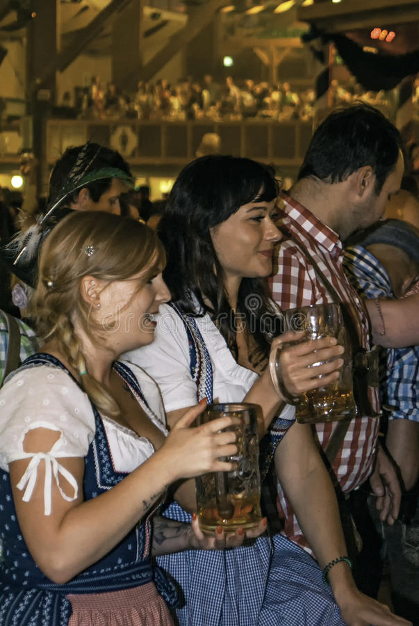 MUNICH, GERMANY - SEPTEMBER 18, 2016: Oktoberfest munich: 2 girls in traditional costumes drinking in the beer pavilion royalty free stock photo