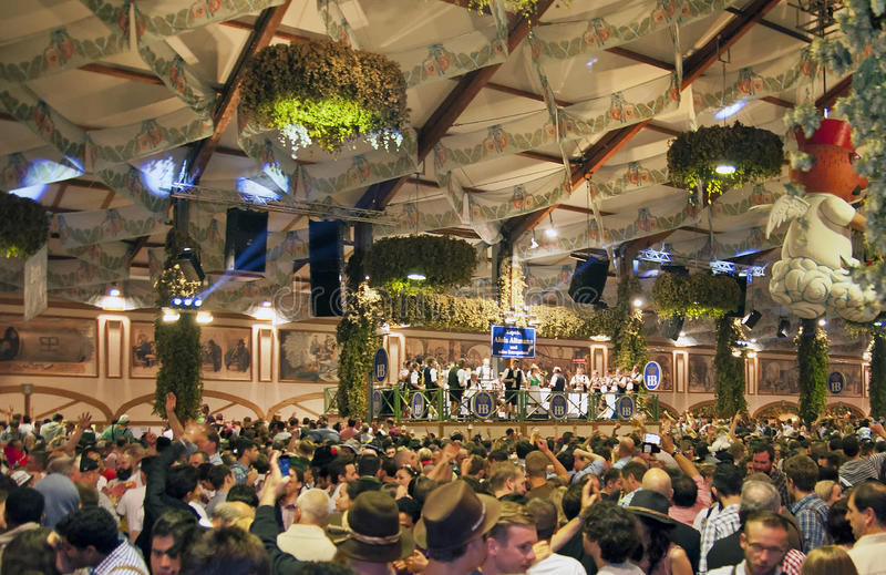 MUNICH, GERMANY - SEPTEMBER 23, 2014: Oktoberfest. Munich: People dressed in traditional costumes sitting in the beer pavilion stock photography
