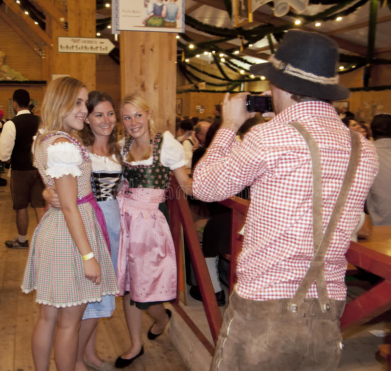 MUNICH, GERMANY - SEPTEMBER 23, 2014: Oktoberfest. Munich: People dressed in traditional costumes taking a photo in the beer pavilion stock photography