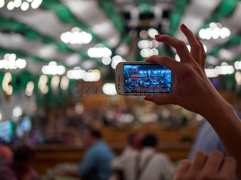 Munich, Germany - September 21: Unidentified girl makes photo of tent on the Oktoberfest with her mobile phone on royalty free stock image