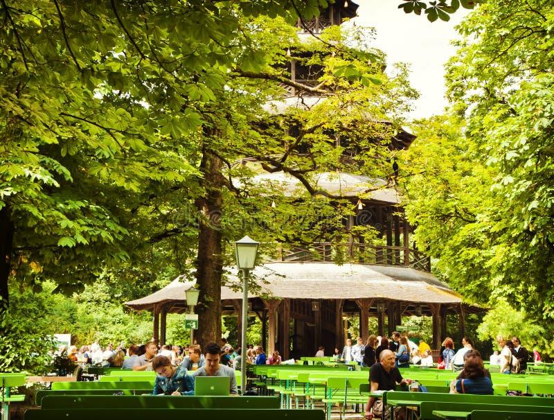 Munich - os povos relaxam fora no jardim chinês da cerveja da torre de E fotografia de stock royalty free