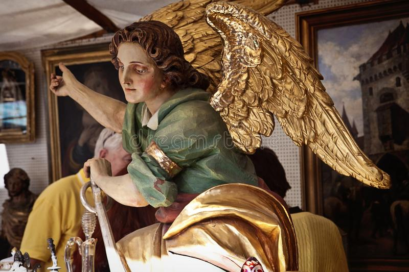 Munich, painted angel statue at Auer Dult open air flea market. MUNICH, GERMANY - -Vintage wooden carved angel on sell at the Auer Dult, one of Munich`s oldest royalty free stock images
