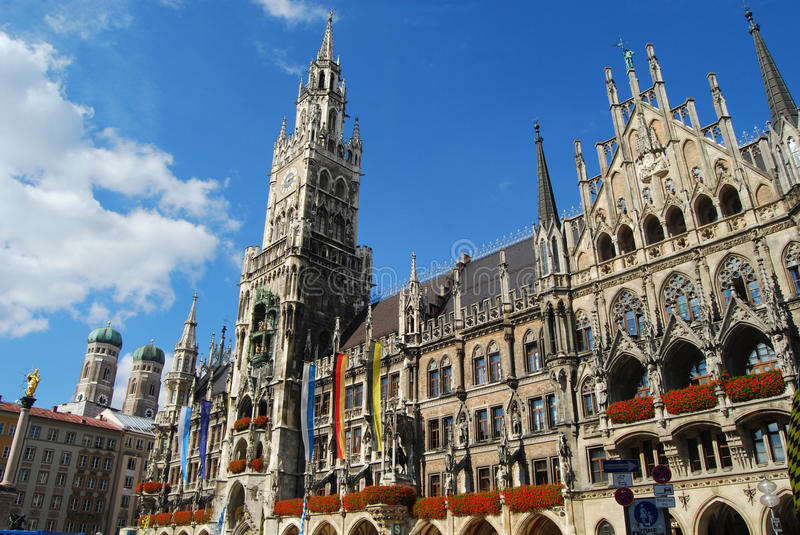 Munich Town Hall and Frauenkirche towers in the sun. Munich Town Hall was built between 1867 and 1908 by Georg von Hauberrisser in a Gothic Revival architectural royalty free stock photo