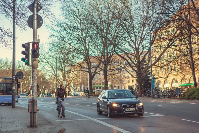 Munich Tyskland, December 29, 2016: En bil och en cyklist står på en trafikljus i Munich Skott på Canon 5D fläck II med främsta L fotografering för bildbyråer