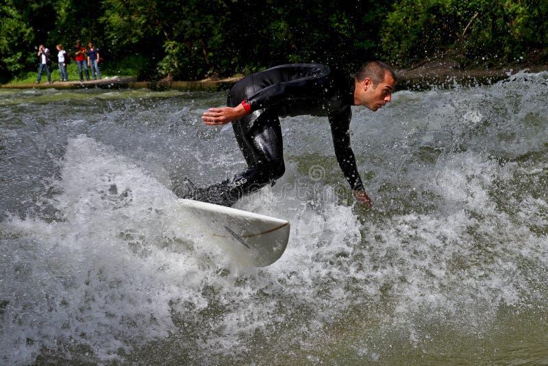 Munich Tyskland - Juli 13, 2019: Surfaren i stadsfloden kallade Eisbach arkivfoto