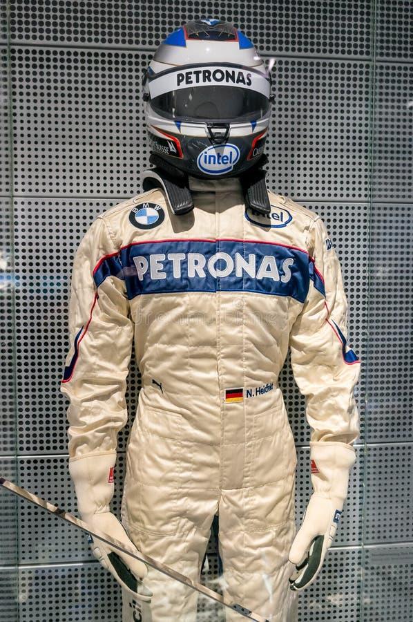 Munich Tyskland - mars 10, 2016: Dräkt för formel en av BMW racerbilchauffören som bär den skyddande läder och hjälmen arkivfoton