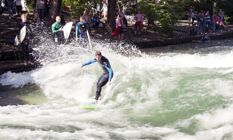 MUNICH TYSKLAND - NOVEMBER 1: Surfare utbildar på en konstgjord våg om 1 meter högt i den på engelska trädgården för den Eisbach  fotografering för bildbyråer
