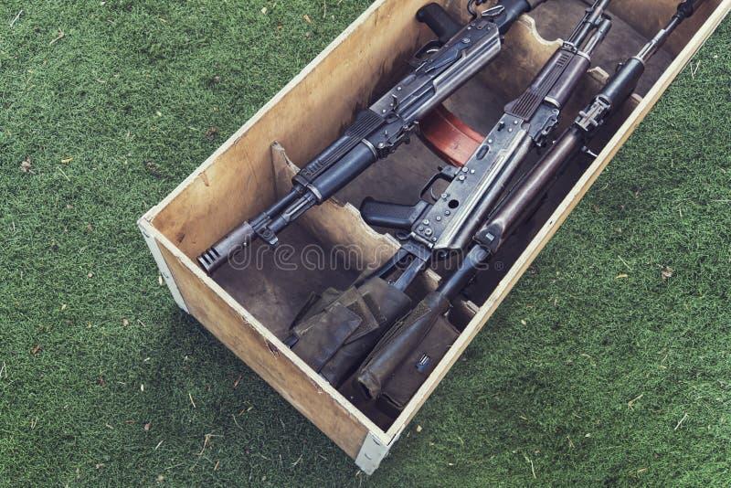 Munición de la caja del ejército con el rifle y la munición de AK47 Un arma automática con un alcance del francotirador en la caj imagen de archivo