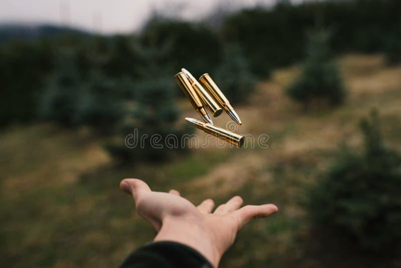 Munición que vuela sobre una mano del hombre Cazador y munición profesionales para cazar Calibre 8x57 Concepto de industria imagen de archivo