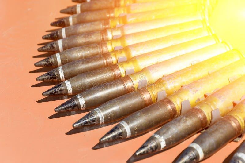 Municiones de los cartuchos del arma en la base oscura de piedra concepto del conflicto militar imagen de archivo