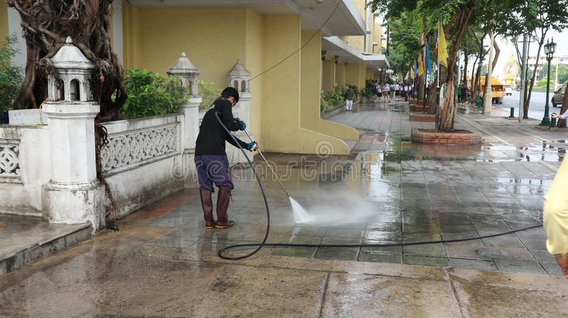 A municipality employee uses a high-pressure washer. BANGKOK, THAILAND - NOVEMBER 10, 2018: A municipality employee uses a high-pressure washer to clean the stock images