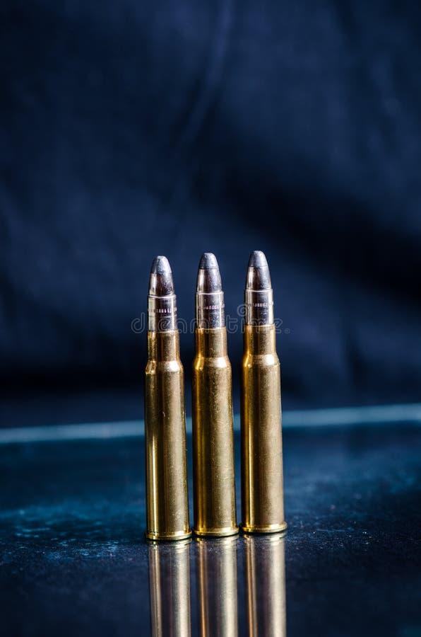 Munitie op een donkerblauwe achtergrond met bezinning in een glas Sluit omhoog wapens kogels stock foto