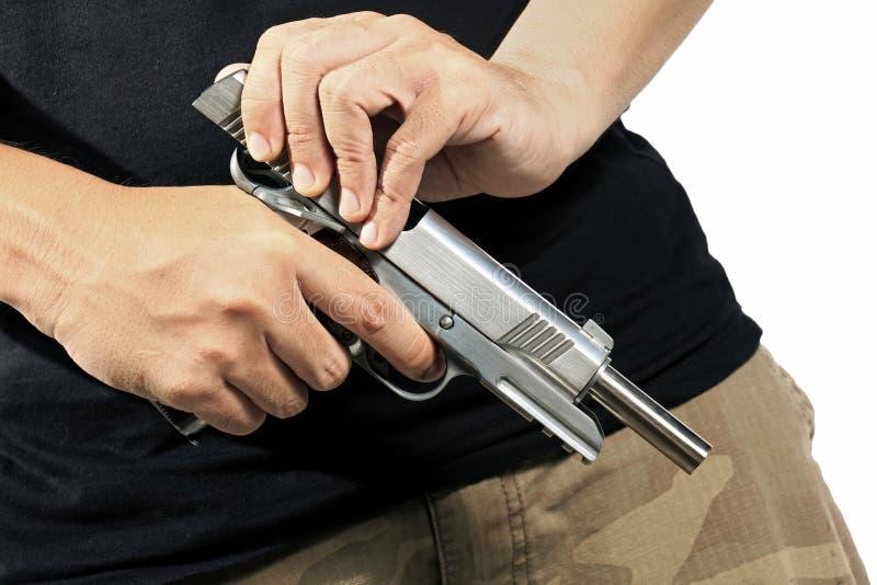 Munizioni della pistola della tenuta e di caricamento dell'uomo fotografia stock
