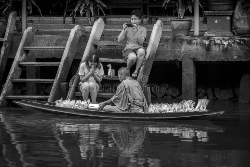 Munk Collecting Alms på den Amphawa floden royaltyfri bild