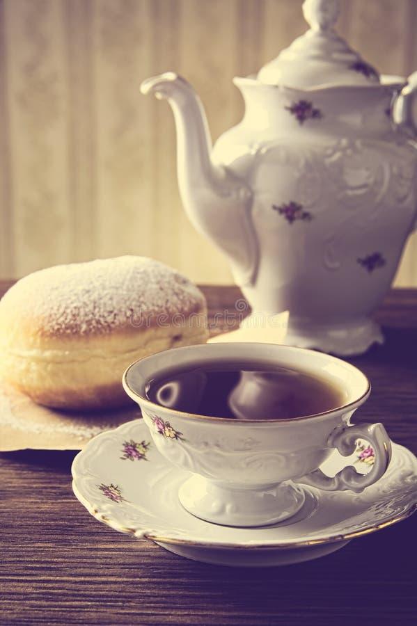 Munk med kopp te på tabellen i gammalmodigt arkivfoto