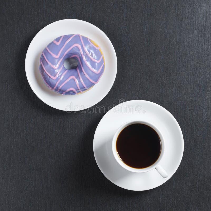 Munk med kulör glasyr och kaffe royaltyfri foto