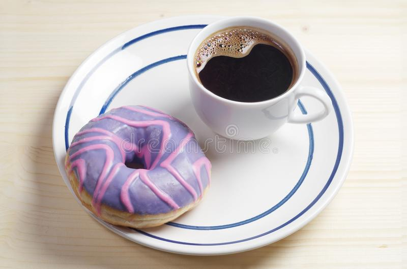 Munk med kulör glasyr och kaffe royaltyfri fotografi